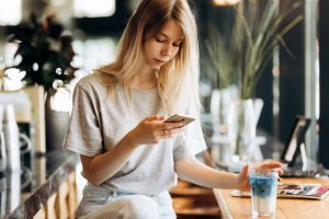 A cute thin blonde girl,dressed in casual style,drinks coffee and looks at her phone in a coffee